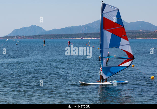 Wind Surfing in the Summer on Calm Coastal Water, Small Island in Background - Stock Image
