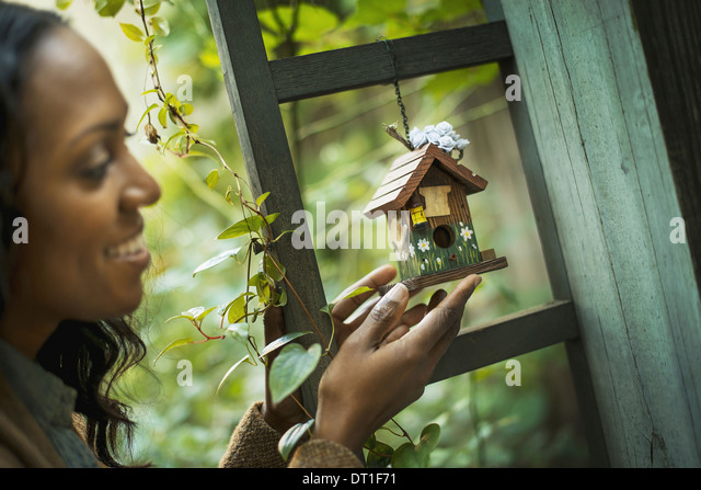 Scenes from urban life in New York City A woman holding a small painted bird house in an enclosure - Stock Image