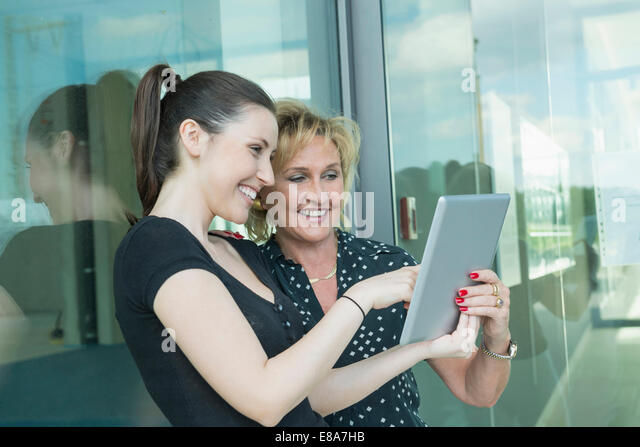 two female colleagues with tablet computer - Stock Image