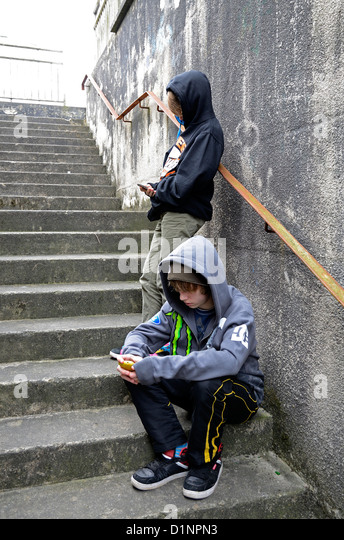 two teenage boys texting using cell phones - Stock-Bilder