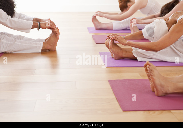 People practicing yoga together in class - Stock Image