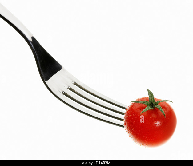 Close up of cherry tomato on fork - Stock Image