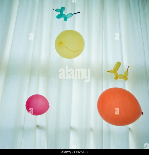 Colourful balloons against white curtain - Stock Image