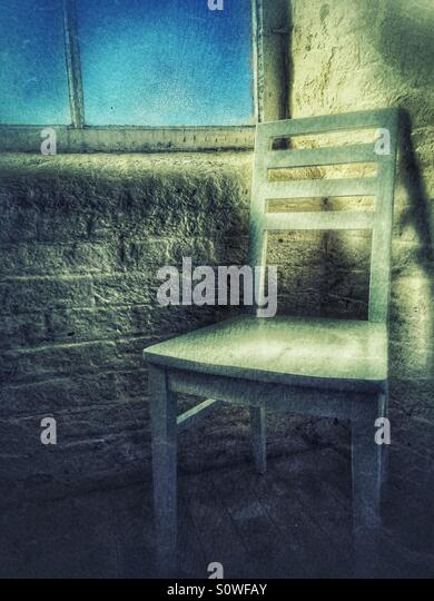 Wooden chair by the window - Stock-Bilder