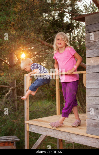 Sweden, Gotland, Faro, Girl (8-9) with brother (2-3) at tree house porch - Stock Image
