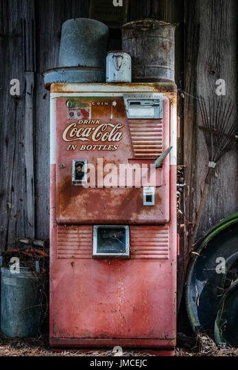 Old beat up Coke-a-Cola drink machine abandoned, against an old wooden building. - Stock Image