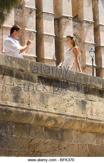 Man taking photograph of woman leaning on ledge - Stock Image