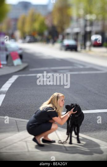 Woman couching on urban sidewalk petting and kissing her dog - Stock-Bilder