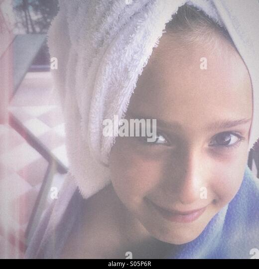 Girl with towel on her head smiling - Stock Image