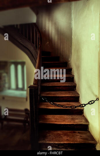 Old staircase wit a chain blocking the way up - Stock Image