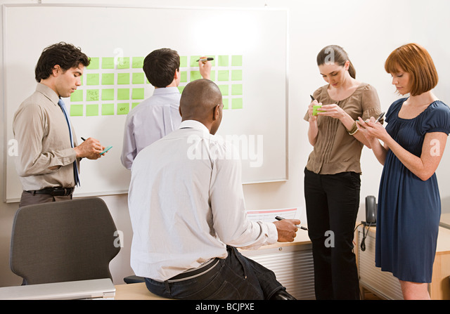 Office workers writing ideas on adhesive notes - Stock Image