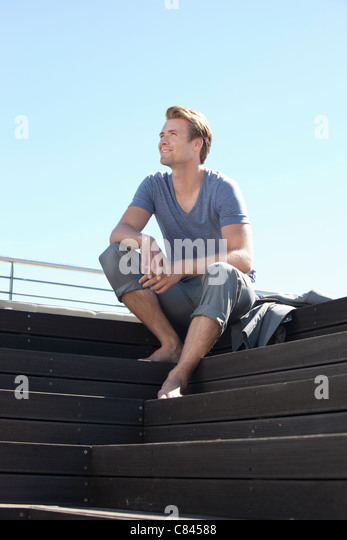 Man relaxing on wooden steps - Stock Image