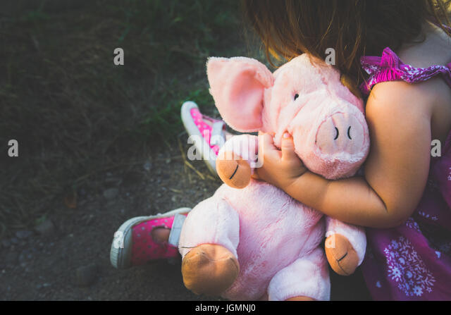 A young female child holds a pink stuffed pig. - Stock Image