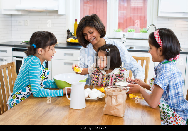 Mother baking with girls in kitchen - Stock-Bilder
