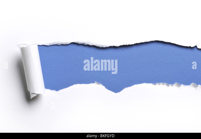 ripped white paper against a blue background - Stock Image