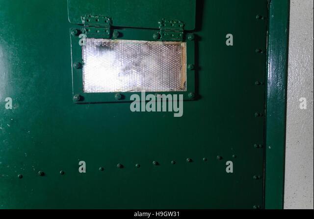 Window on a green prison door - Stock Image