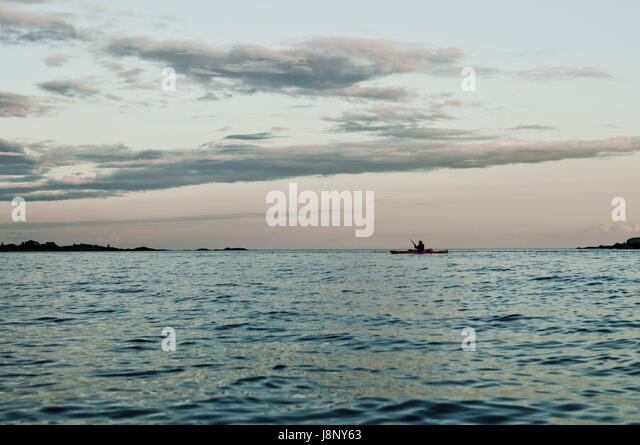 Seascape with silhouette of man in rowing boat - Stock-Bilder