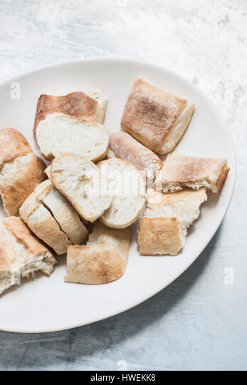 Studio shot, overhead view of plate with sliced baguette and flat bread - Stock-Bilder
