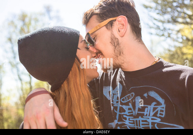 Couple kissing, woman wearing knit hat - Stock Image