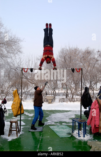 A middle aged Chinese woman doing early morning gymnastics in Stalin Park Harbin in China winter 2005 - Stock Image