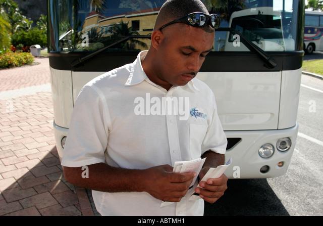 Sint Maarten Philipsburg Dutch Black male bus driver counts tickets - Stock Image