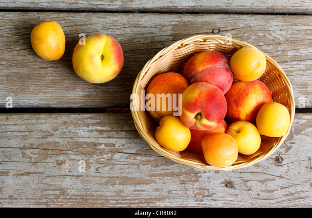 Juicy peaches and apricots in basket - Stock Image