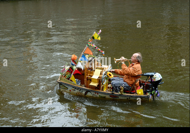 A busker playing trumpet in a small boat on a canal in Amsterdam. Stock Photo