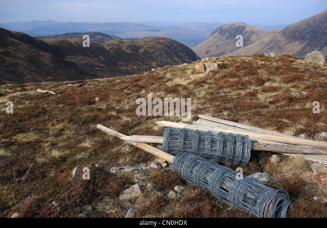 Rolls of stock fencing on a hillside in the Nevis range of mountains in Scotland - Stock Image