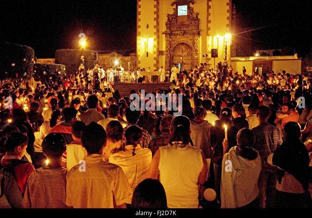 Devout ;CATHOLICS light candles during EASTER MASS at SAN ANTONIO CHURCH - SAN MIGUEL DE ALLENDE, MEXICO - Stock-Bilder