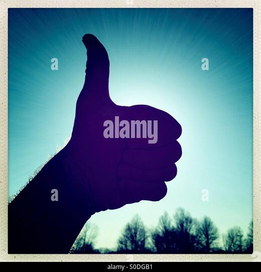 Big thumbs up silhouette in morning rays of sunshine - Stock Image