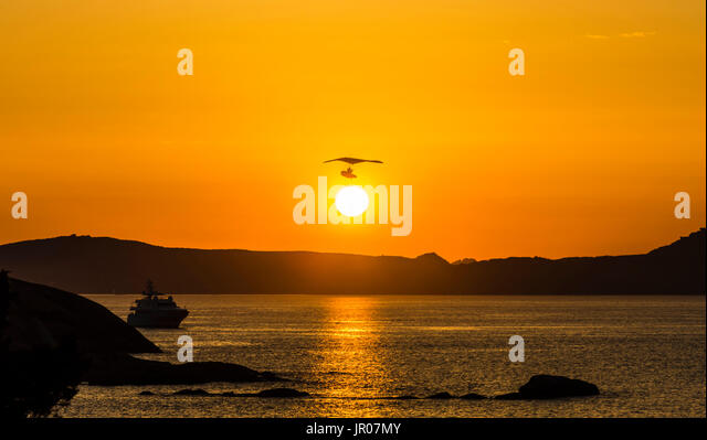 Flying boat over the sun in an orange sunset over Sardinia, Italy - Stock Image