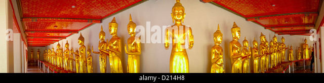 panoramic view of gold standing Buddhas in Wat Po, Giant Reclining Buddha Temple, in Bangkok, Thailand. - Stock Image