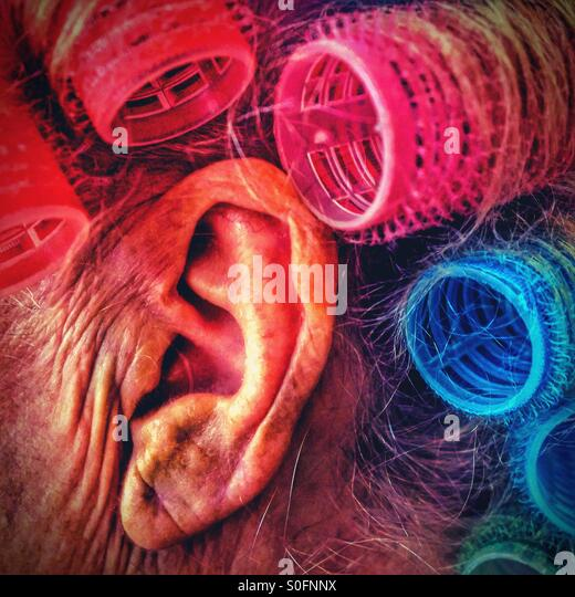 Senior persons ear with coloured hair rollers - Stock Image