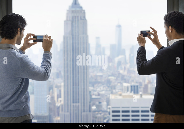 Two young men using their phones to take images of the city from an observation platform overlooking the Empire - Stock Image