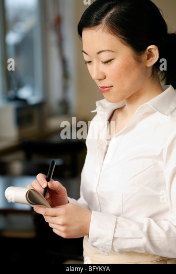 portrait of japanese waitress taking an order - Stock Image