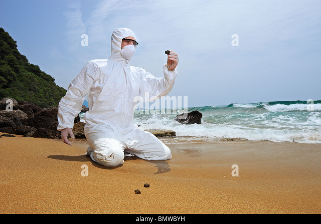 Worker in a protective suit examining pollution at the beach - Stock Image