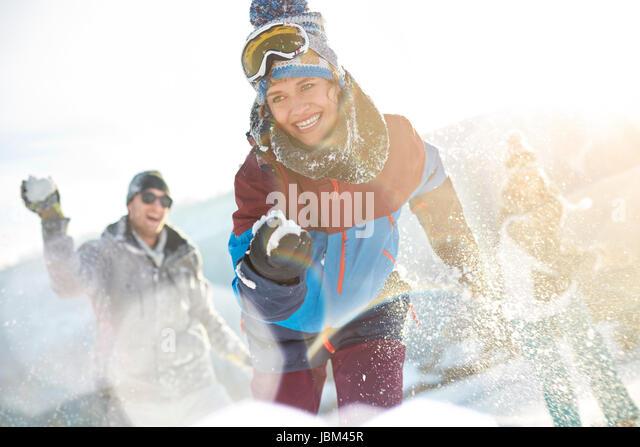 Playful friends enjoying snowball fight in sunny field - Stock-Bilder
