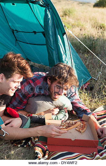 Young men eating pizza in tent - Stock Image