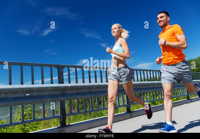smiling couple running at summer seaside - Stock-Bilder