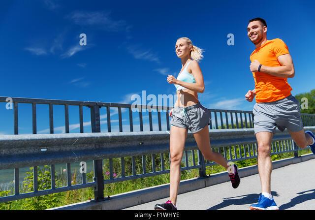 smiling couple running at summer seaside - Stock-Bilder