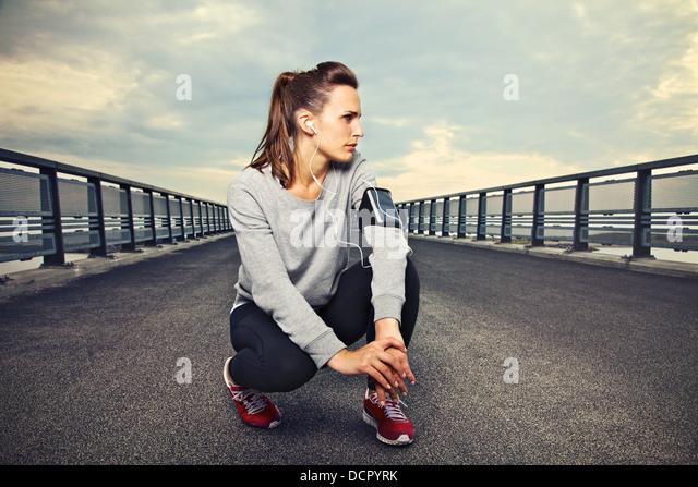 Female fitness runner sitting alone on the bridge resting - Stock Image