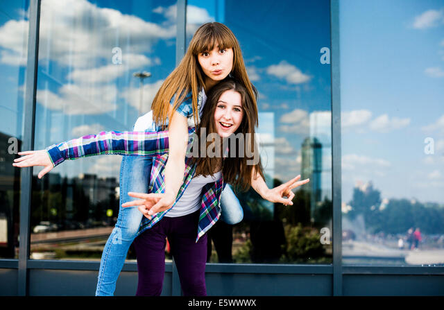 Two young women piggybacking and making peace signs - Stock-Bilder
