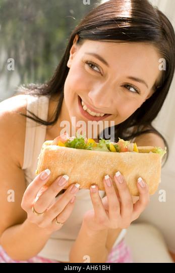 Brunette girl eating healthy sandwich - Stock-Bilder