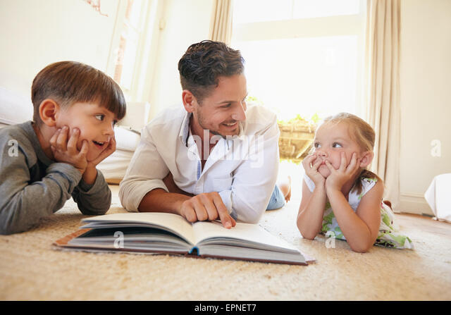 Indoor shot of young man with two kids reading a story book. Family lying on the floor with a book in living room. - Stock Image
