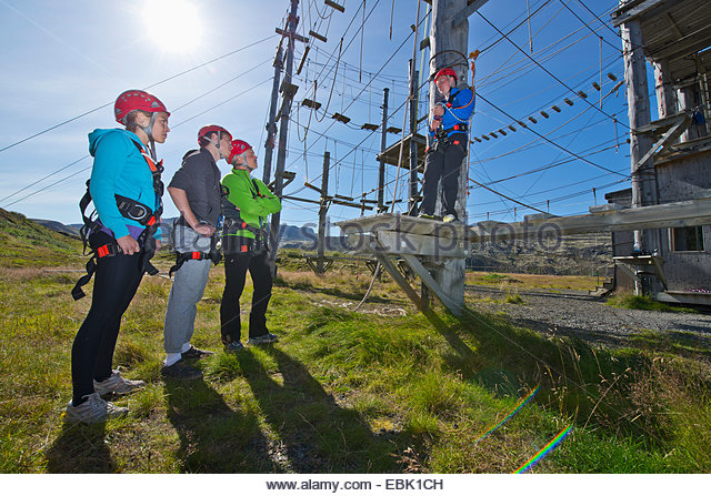 Four people wearing climbing helmets on high rope course - Stock Image
