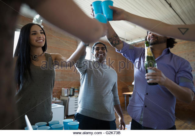 Creative business people celebrating toasting champagne in office - Stock Image