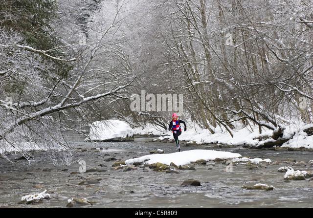 A jogger crossing a snowy alpine river - Stock-Bilder