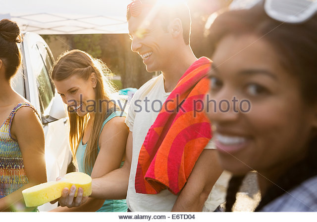 Portrait of friends washing car - Stock Image