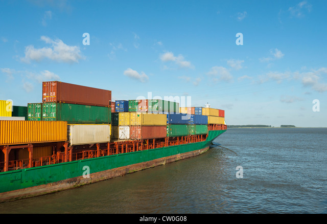 Container ship sailing into harbor - Stock Image