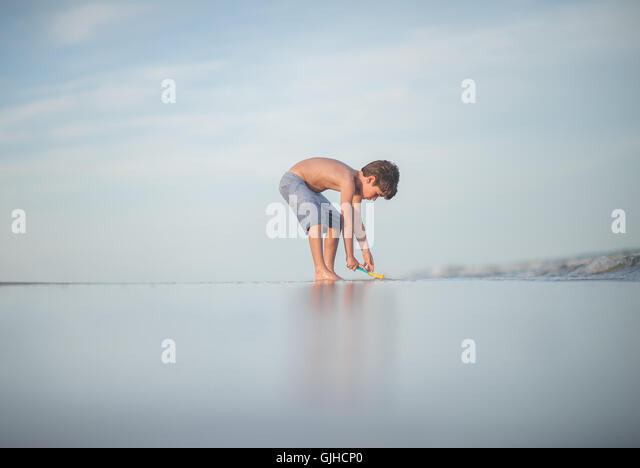 Boy digging on beach, Florida, America, USA - Stock Image